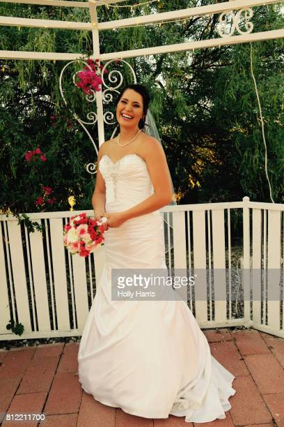 Bride laughing, standing in a gazebo