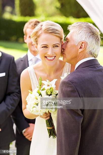 Bride Looking Away While Father Kissing Her On Cheek