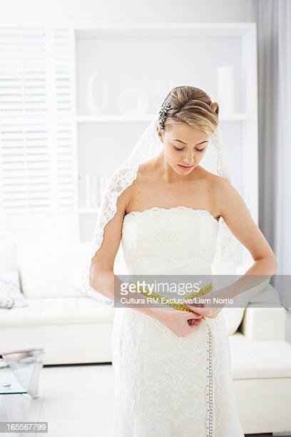Bride measuring her waistline