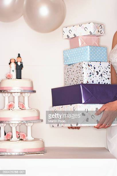 Bride placing presents on table by wedding cake