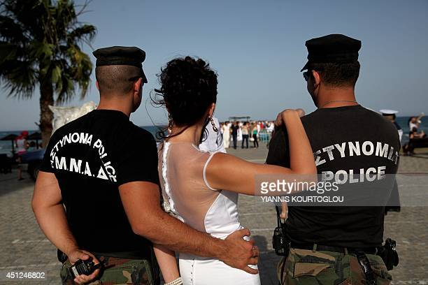 A bride poses with two Cypriot policemen in Larnaca's seaside promenade after a mass civil wedding ceremony for foreign couples organised by the...