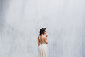 Bride posing in front of a white painted wall in the studio