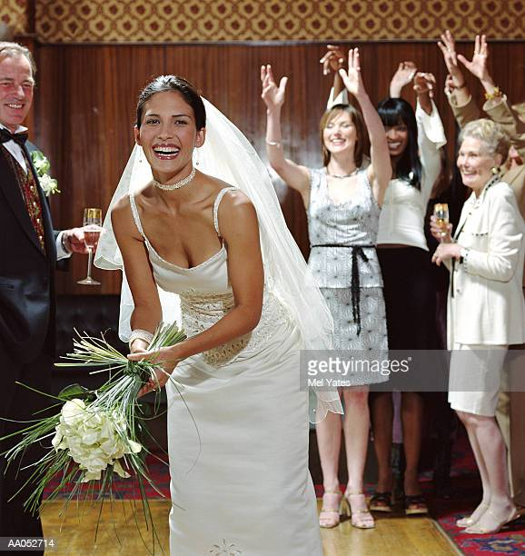 Bride preparing to toss bouquet to female reception guests