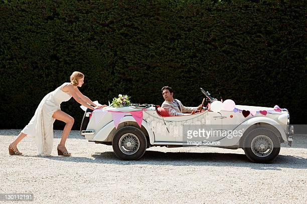 Bride pushing broken down vintage car