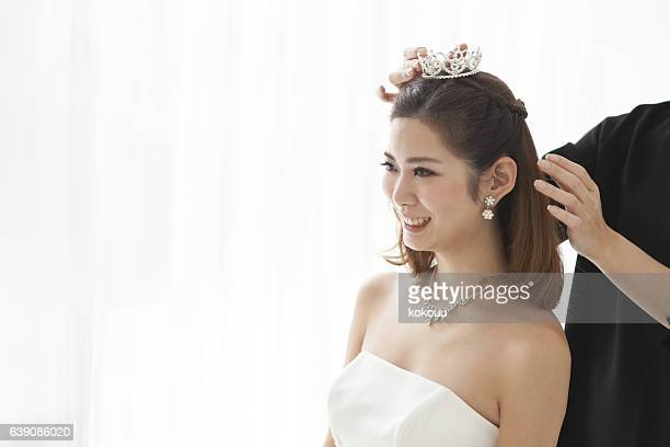 Bride puts a crown on her head.