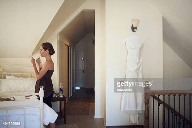 Bride Putting on Makeup Before Wedding