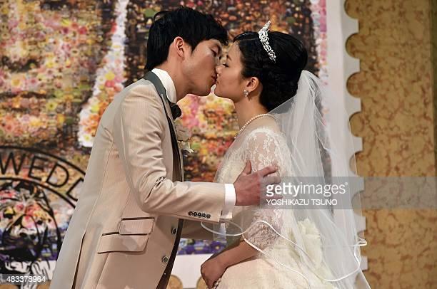 Bride Rie Oka and groom Kazuya Fukushima kiss during their wedding ceremony at the Mitsukoshi department store in Tokyo on August 8 2015 Mitsukoshi...