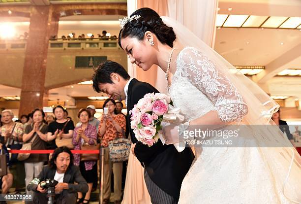 Bride Rie Oka and her father Kazuyoshi Oka arrive for a wedding ceremony at the Mitsukoshi department store in Tokyo on August 8 2015 Mitsukoshi and...