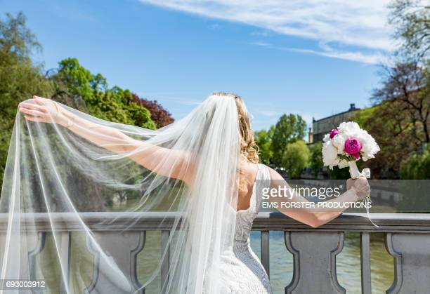 bride seen from behind wearing her white wedding dress with train while holding her bridal bouquet of flowers consisting of white and pink peony flowers in her right hand  - she stands on a Isar bridge in Munich on a sunny day