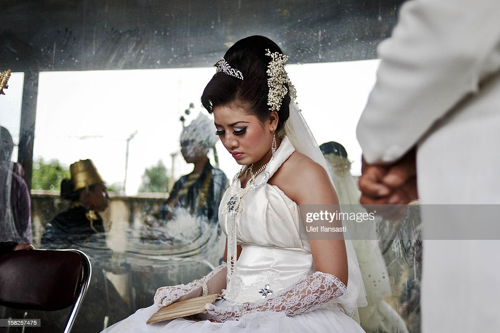 A bride sits during a mass wedding ceremony on December 12, 2012 in Yogyakarta, Indonesia. Twelve couples participated in a mass wedding as today saw a surge in marriage across the globe to mark the once in a century date of 12/12/12.