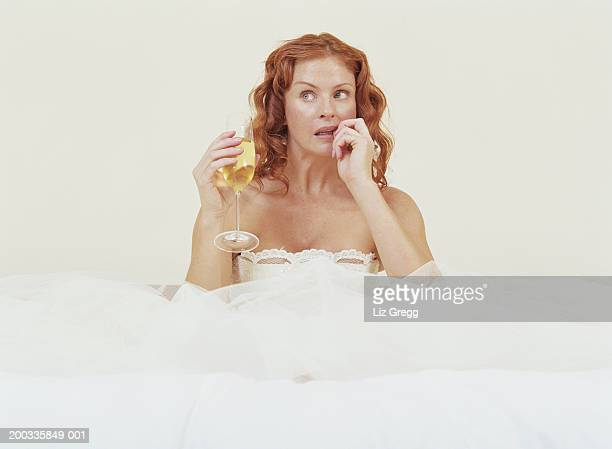 Bride sitting amongst netting of dress, holding glass of champagne