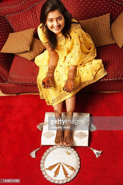 Bride sitting on a couch with henna decoration and smiling