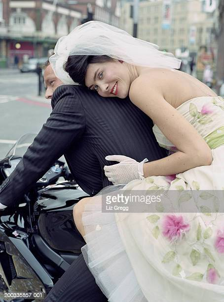 Bride sitting on back of motorbike with groom, smiling, portrait