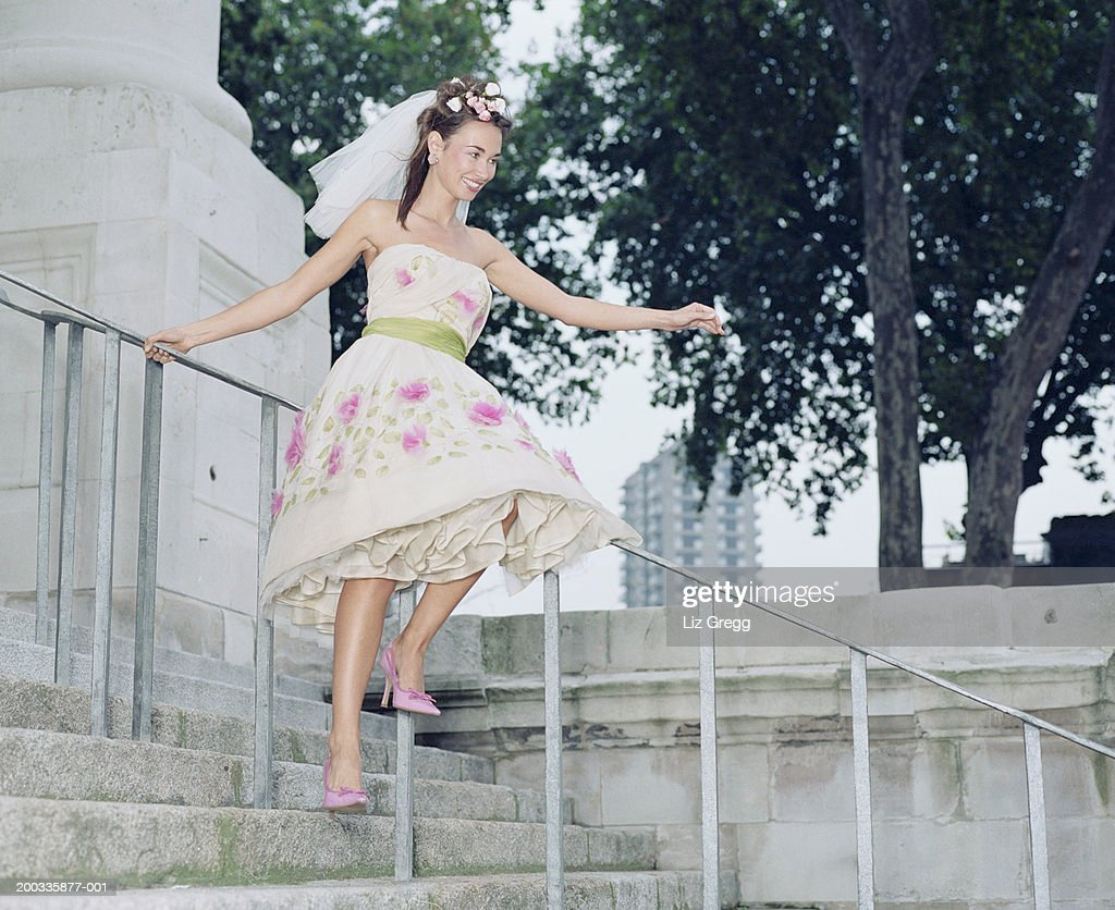 Bride sitting on rail of church steps, smiling : Stock Photo