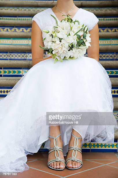 Bride sitting on steps with bouquet neck down