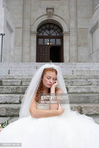 Bride sitting on stone steps, hand to face, looking towards ground