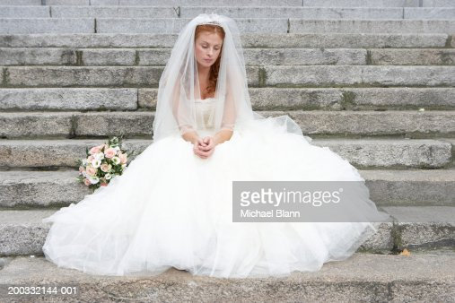 Bride sitting on stone steps, looking towards ground