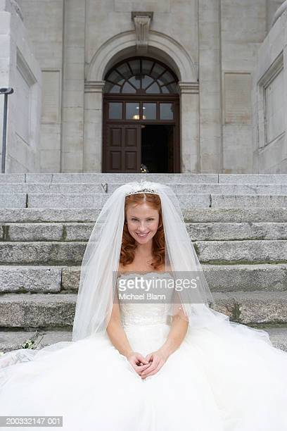 Bride sitting on stone steps, smiling, portrait