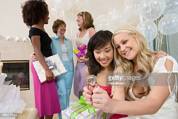 Bride sitting with her Friend looking at large engagement ring at Bridal Shower