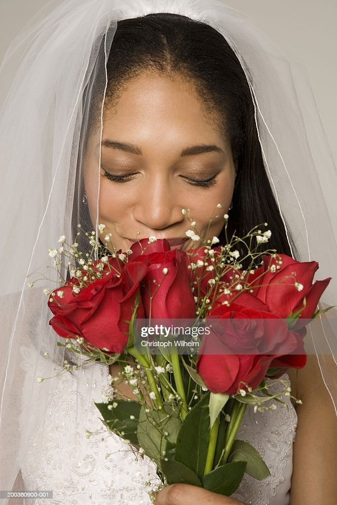 Bride smelling bouquet of roses : Stock Photo