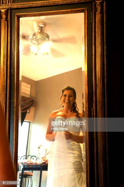 Bride smiling and laughing as she looks in mirror
