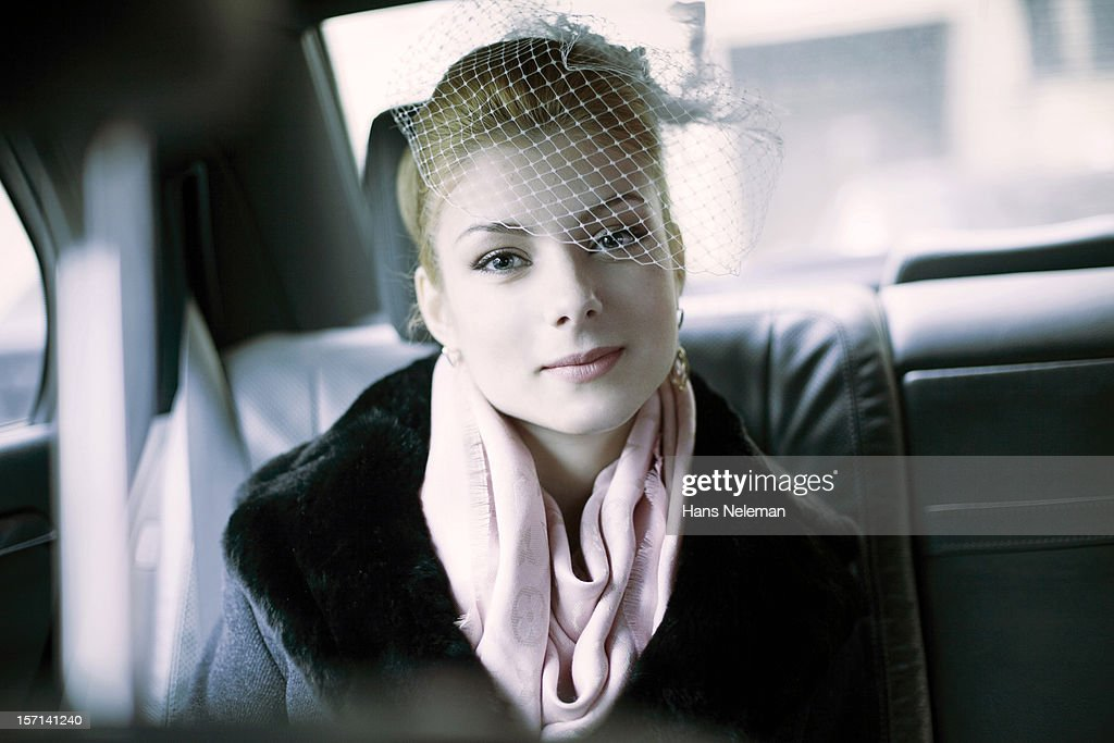 Bride smiling in back of car, portrait : Stock Photo