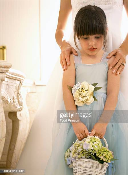 Bride standing beside flower girl (3-5), hands on girl's shoulders