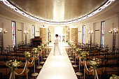 Bride standing in aisle lined with flowers in empty church, side view