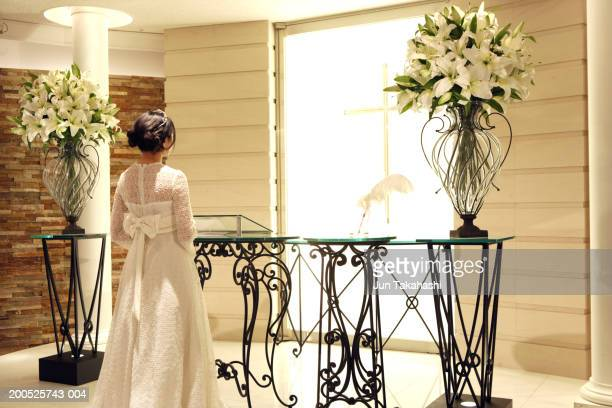 Bride standing on altar in church, rear view