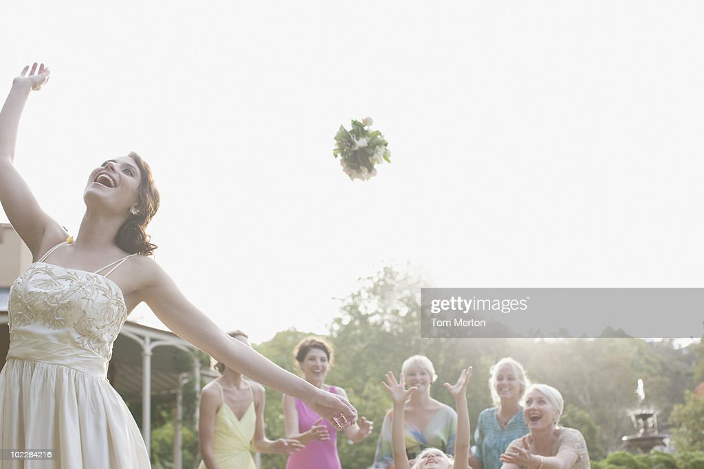 Bride throwing bouquet at wedding reception : Stock Photo