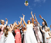 Bride Throwing Bouquet Outdoors For Guests To Catch