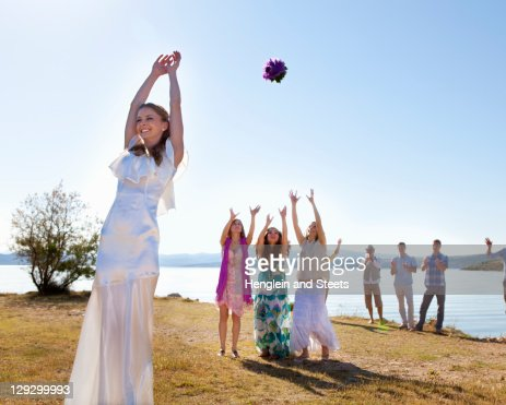 Bride throwing bouquet to friends : Stock Photo