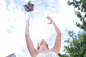 Bride throwing flower bouquet at wedding