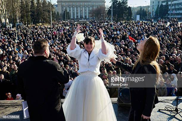 A bride throws her bouquet to the crowd as ProRussian rebels and Donetsk residents attend a rally to celebrate the Russian festival 'Defender of the...