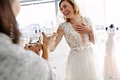 Cheerful young woman in wedding gown toasting champagne with friends in bridal Boutique. Beautiful bride in elegant wedding dress clinking glasses of champagne with her friends and smiling in wedding