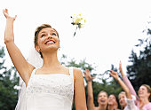 Bride tossing bouquet, women with arms raised in background