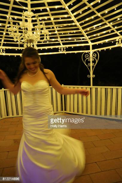 Bride twirling in gazebo at night, blurred motion