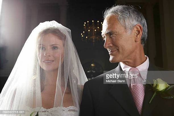 Bride walking down aisle, arm linked with father's, smiling, close-up