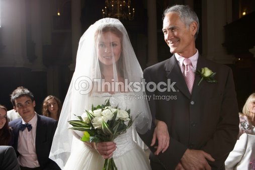 Bride Walking Down Aisle Arm Linked With Father S Smiling Stock Photo