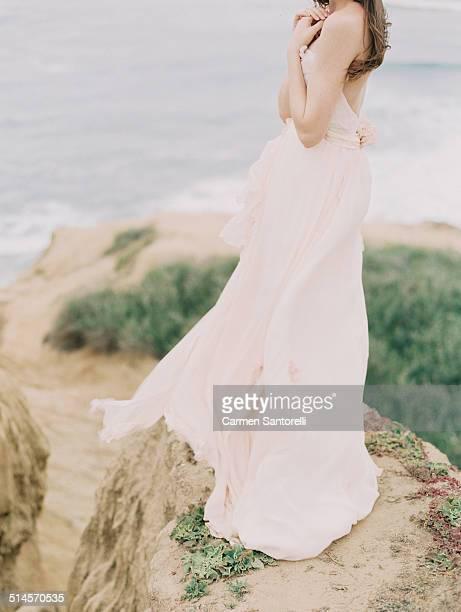 Bride wearing a blush gown on a cliff edge