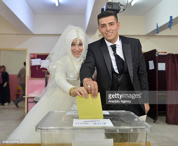 A bride wearing a wedding dress and a groom wearing a wedding suit cast their ballot at a polling station during Turkey's 25th general election in...