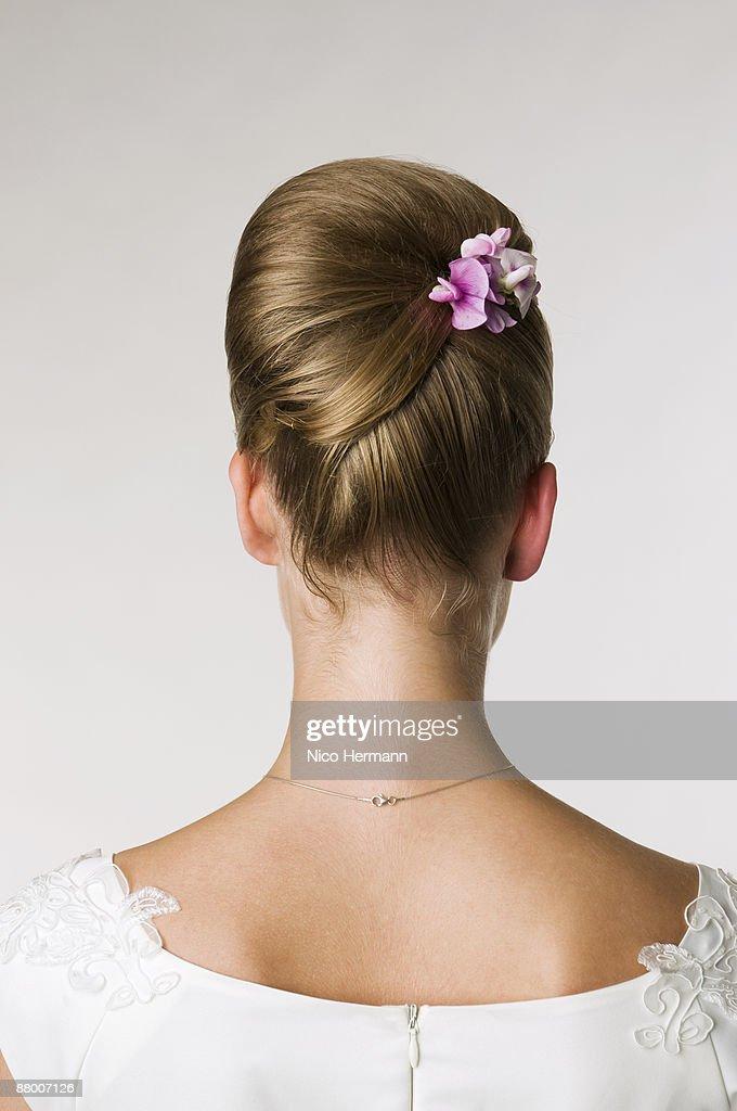 Bride wearing flower in hair, rear view