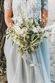 Bride wearing light blue wedding dress holding bouquet for a beach wedding