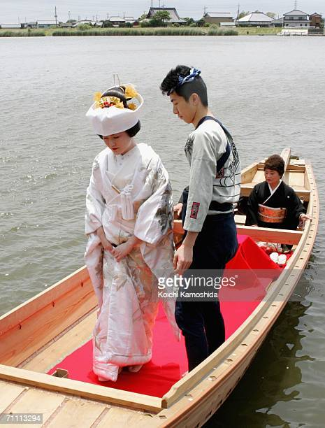 A bride wearing the traditional Japanese bride's costume travels on a boat on the Kitatone River on June 3 2006 in Itako Japan It has been the custom...