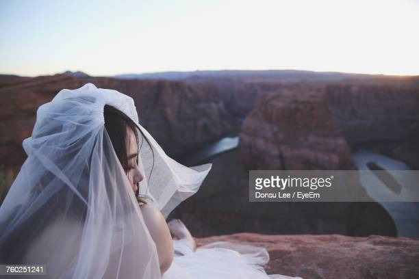 Bride Wearing Veil Sitting On Rock At Glen Canyon National Recreation Area