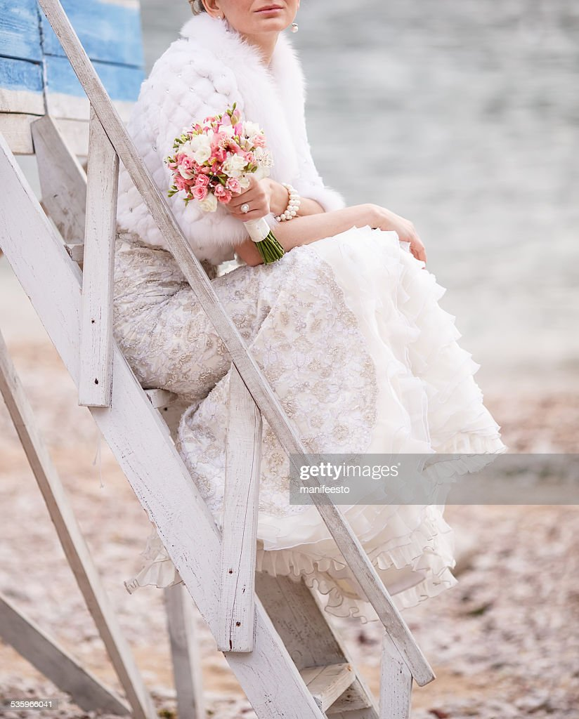 Bride with bouquet by  shore posing on a ladder. : Stock Photo
