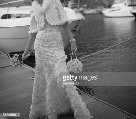 Bride with bouquet walking on pier near  yacht. : Stock Photo