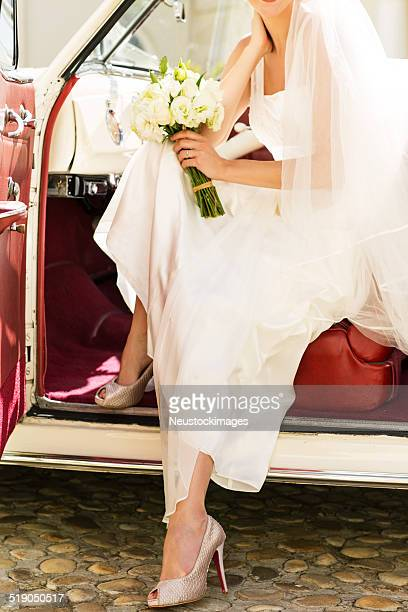 Bride With Flower Bouquet Disembarking From Car