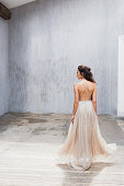 Bride with long black hair in the studio, a photo from the back