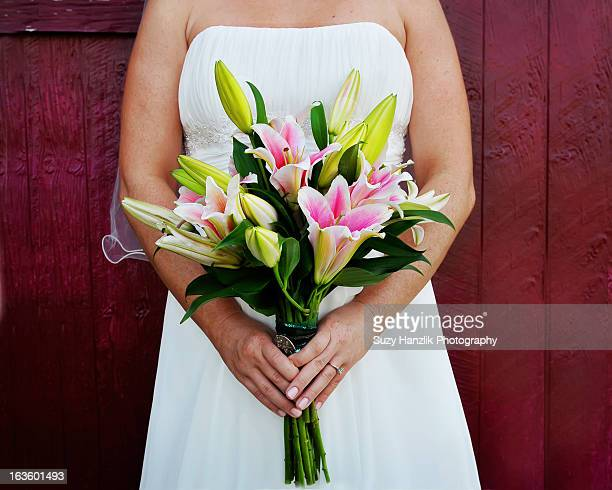 bride with stargazer lilly flowers at barn
